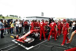 L'équipe Ferrari essaie de réparer la voiture de Kimi Räikkönen sur la grille, sous les yeux du journaliste Jonathan Noble