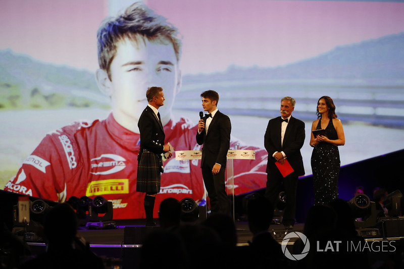Charles Leclerc is presented with the rookie of the year award by Chase Carey