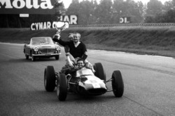 Race winner Jim Clark, Lotus 25 gives Colin Chapman, Lotus Team Owner a lift round the circuit