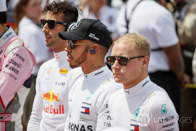 Daniel Ricciardo, Red Bull Racing, Lewis Hamilton, Mercedes AMG F1, and Valtteri Bottas, Mercedes AMG F1, stand for the national anthem on the grid