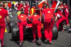 Des mécaniciens de Ferrari poussent la Ferrari SF71H