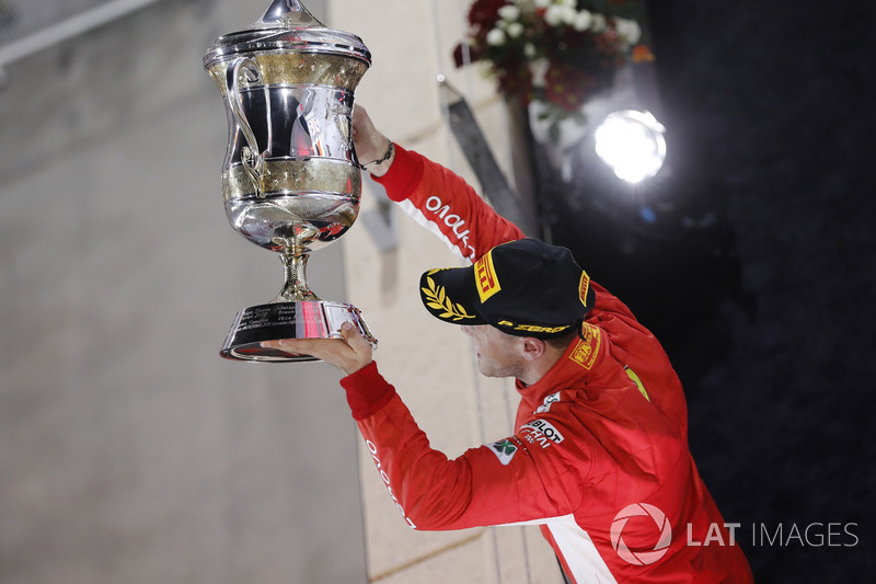 Sebastian Vettel, Ferrari, 1st position, holds up his trophy on the podium