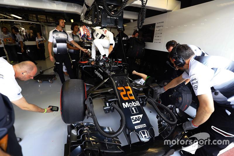 Jenson Button, McLaren enters his cockpit in the garage