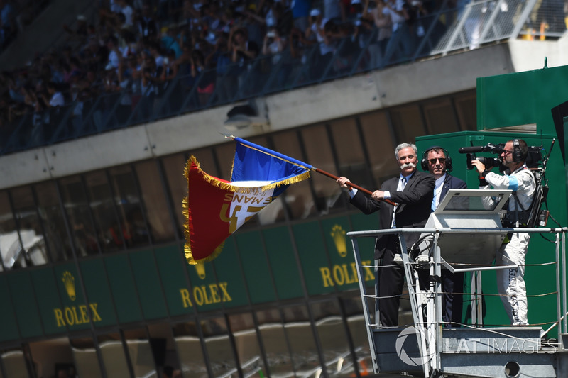 Chase Carey, FOM CEO waves the French flag to give the start of the race