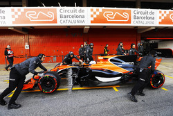 McLaren team members push the McLaren MCL32 of Fernando Alonso, McLaren, in the pit lane