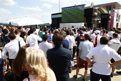Fans and team members gather around a screen for the England v Sweden World Cup game
