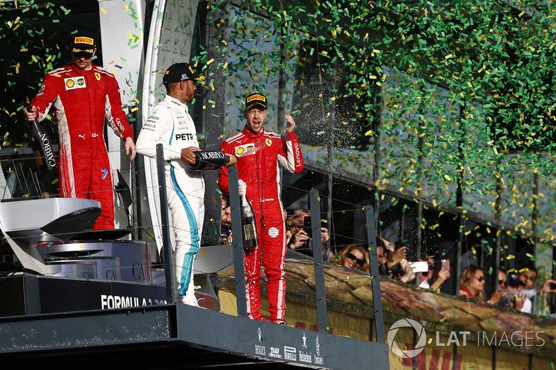 Kimi Raikkonen, Ferrari, 3rd position, Lewis Hamilton, Mercedes AMG F1, 2nd position, and Sebastian Vettel, Ferrari, 1st position, celebrate with Champagne on the podium