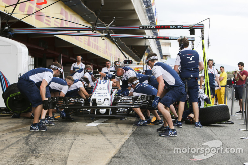 Williams mechanics practice their pit stops in the pit lane