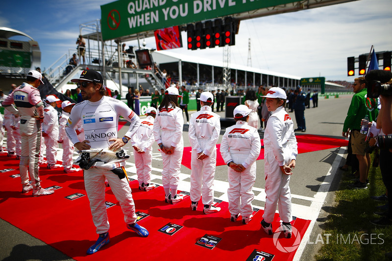 Esteban Ocon, Force India, and Fernando Alonso, McLaren, say hello to the Grid Kid mascots