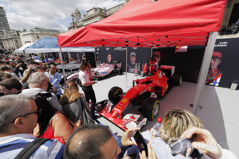 Fans inspect and photograph the Ferrari SF70H on the Scuderia Ferrari stand