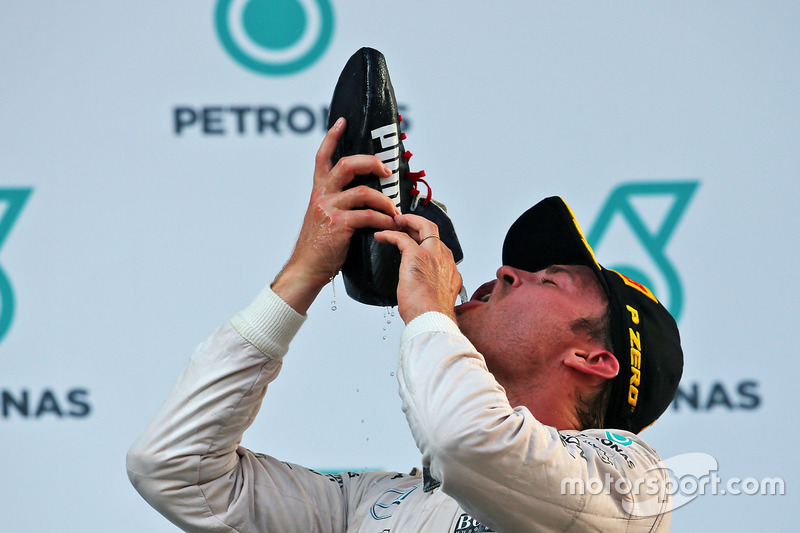 Nico Rosberg, Mercedes AMG F1 drinks from the race boot of Daniel Ricciardo, Red Bull Racing on the
