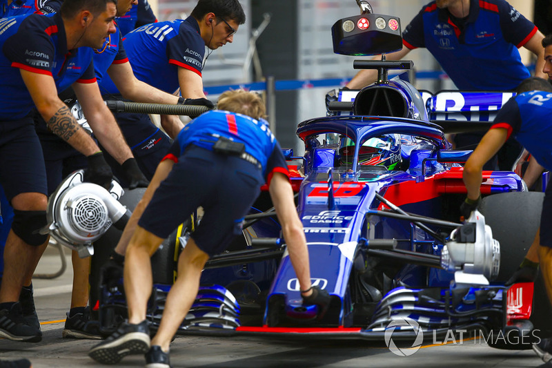 Toro Rosso engineers move Brendon Hartley, Toro Rosso STR13 Honda, to the garage