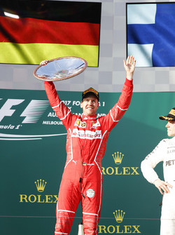 Sebastian Vettel, Ferrari, 1st Position, celebrates victory on the podium with his trophy