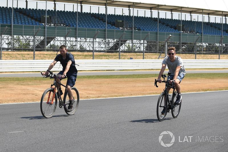 Guy Martin, e Jenson Button, McLaren, vanno in bici lungo il circuito