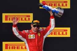 Kimi Raikkonen, Ferrari celebrates on the podium with the trophy