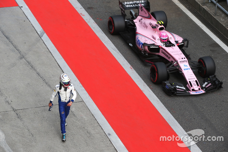 Antonio Giovinazzi, Sauber C36, is passed in the pit lane by Esteban Ocon, Force India VJM10, after a crash in qualifying