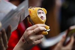 A fan holds a Fernando Alonso, McLaren, mascot