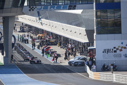 Cars wait in the pit lane