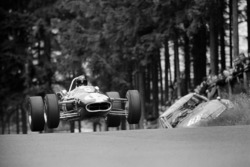 Dan Gurney aviates his Eagle-Climax T1G past the remains of a crashed touring-car at Bruennchen