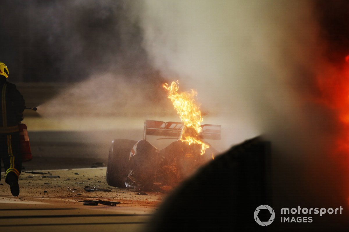 A fire marshal extinguishes the flames on the car of Romain Grosjean, Haas VF-20