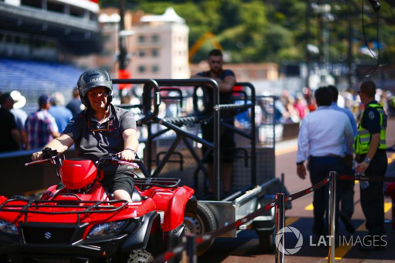 A Haas F1 Team member on a quad bike tows a trailer
