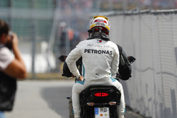Lewis Hamilton, Mercedes AMG F1, rides back to the pits on the back of a motorcycle