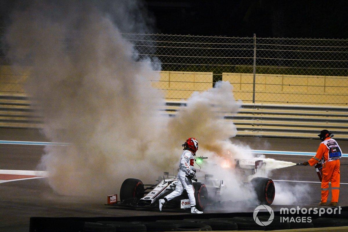 Kimi Raikkonen, Alfa Romeo Racing C39, ayuda a un oficial de pista a apagar el incendio de su monoplaza