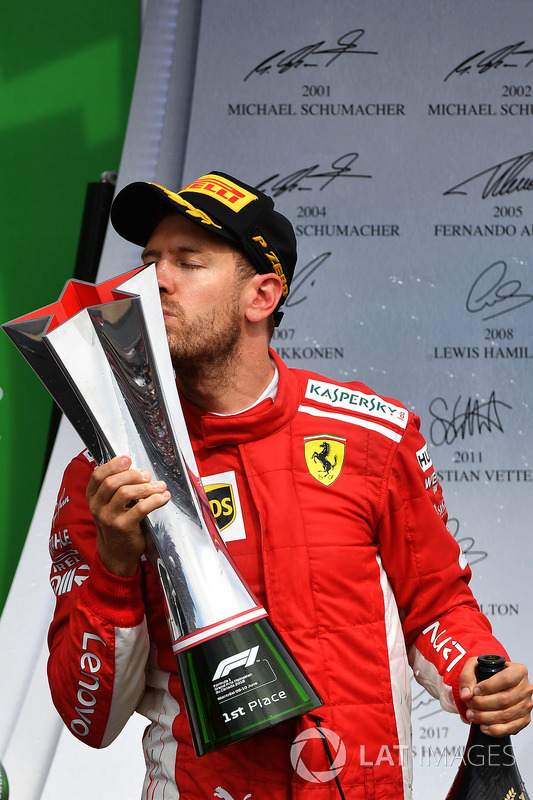 Race winner Sebastian Vettel, Ferrari celebrates on the podium and kisses the trophy