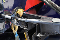 The crashed car of Carlos Sainz Jr., Scuderia Toro Rosso STR12 in the garage after FP1 shwoing broken suspension and wheel tethers