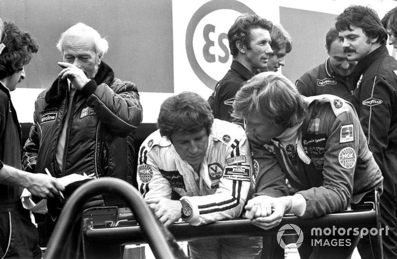 Mario Andretti et Ronnie Peterson discutent avec le patron de l'écurie Lotus, Colin Chapman