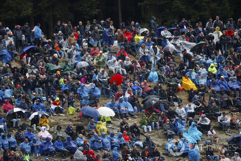 Spectators wear rain gear
