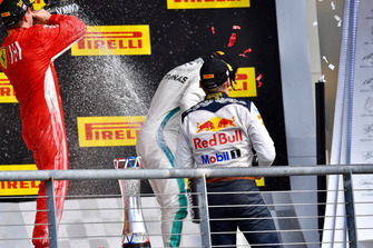 (Da sx a dx): Kimi Raikkonen, Ferrari, Lewis Hamilton, Mercedes AMG F1 e Max Verstappen, Red Bull Racing festeggiano con lo champagne, sul podio