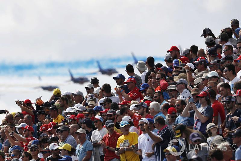 La multitud observa mientras el equipo de acrobacias aéreas de la Fuerza Aérea Francesa, La Patrouille de France, pasa volando en su Dassault Alpha Jet Es