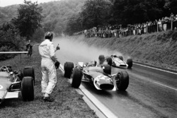 Jo Siffert, Lotus has just stopped for borrowing a dry visor from retired Graham Hill. John Surtees, Honda is passing the pair