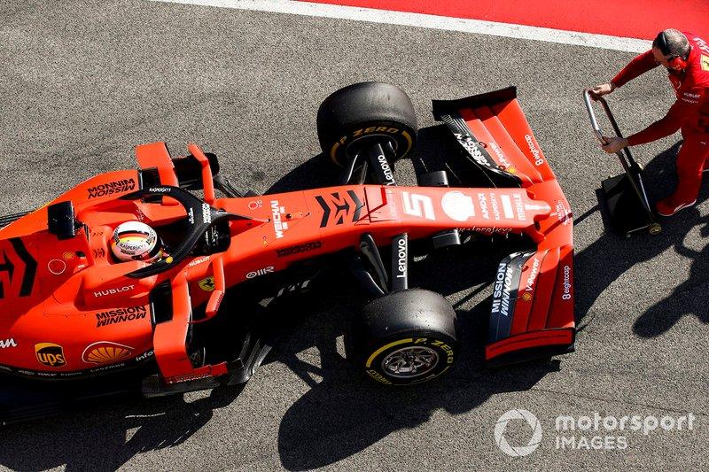 Sebastian Vettel, Ferrari SF90, is attended to by a mechanic in the pit lane