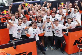 Miguel Oliveira, Can Oncu, and Red Bull KTM Ajo team members celebran