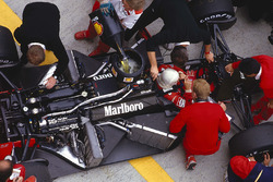 Alain Prost sits in his McLaren MP4/3 TAG Porsche while the mechanics get to work on the car and refuel