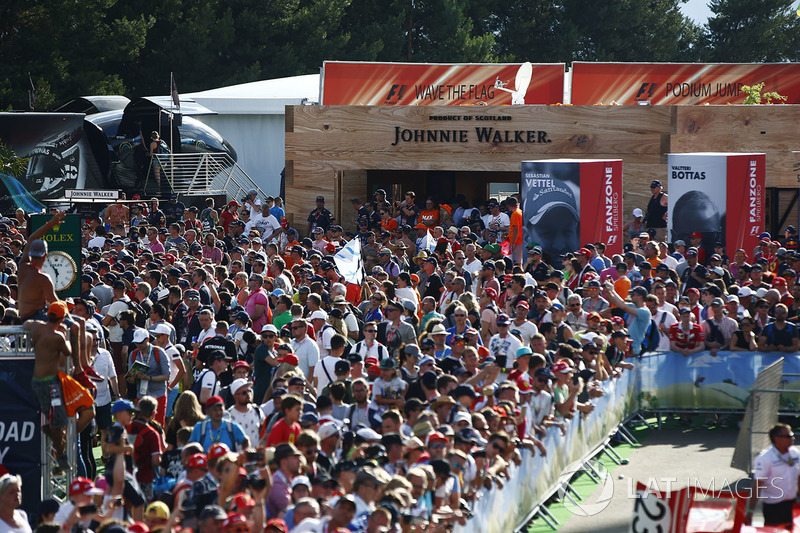Fans gather between a Johnnie Walker bar and a classic car paddock