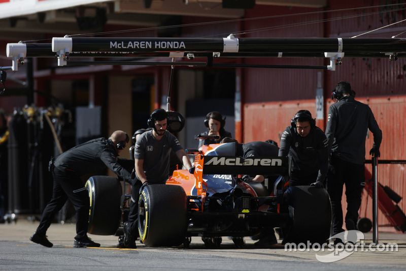 Fernando Alonso, McLaren MCL32, is attended to by mechanics in the pits