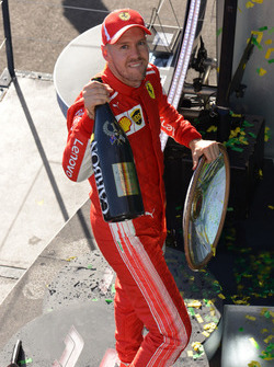 Race winner Sebastian Vettel, Ferrari celebrates on the podium with the trophy and the champagne