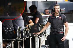 A Haas F1 team member checks for rain