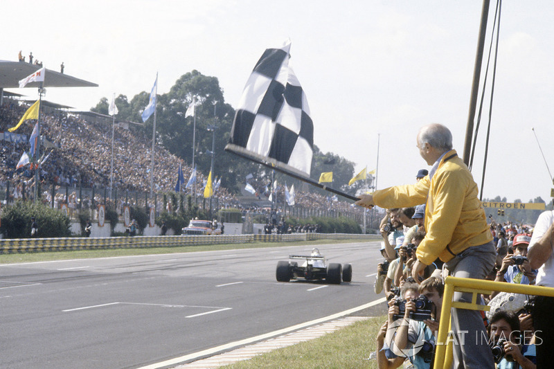 Juan Manuel Fangio sventola la bandiera a scacchi a Carlos Reutemann, Williams FW07C-Ford Cosworth