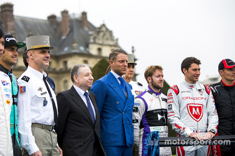 Officials and drivers pose with the iceberg livery on a Formula E car that will be auctioned off to raise money to fight climate change