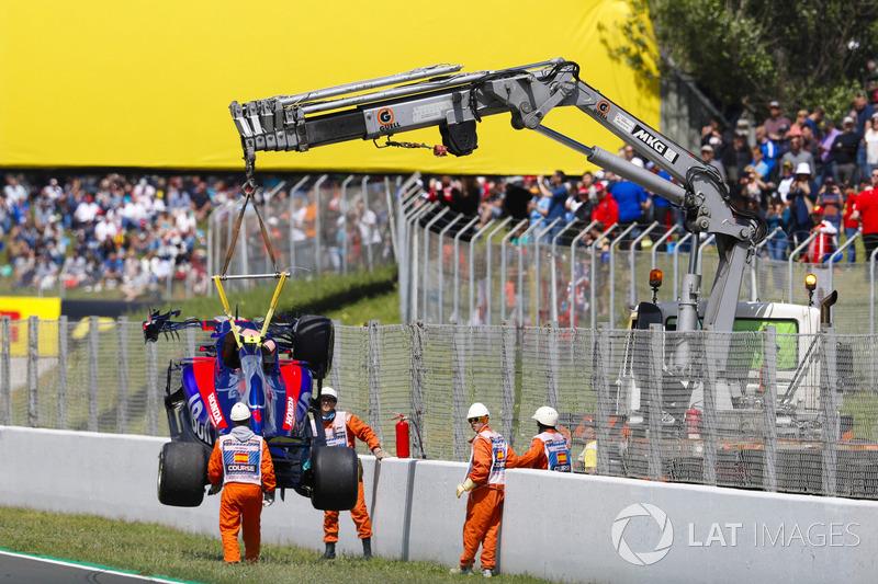 El coche dañado de Pierre Gasly, Toro Rosso STR13, es retirado de la pista por oficiales