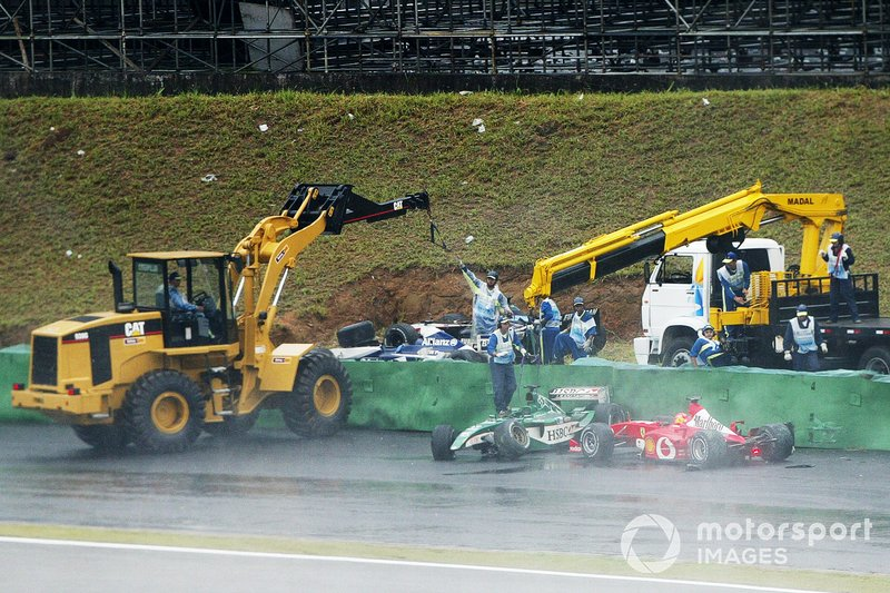 Schumacher sort de la piste alors qu'une grue retire la Jaguar accidentée de Pizzionia.