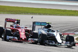 (L to R): Kimi Raikkonen, Ferrari SF16-H and Nico Rosberg, Mercedes AMG F1 W07 Hybrid make contact as they battle for position