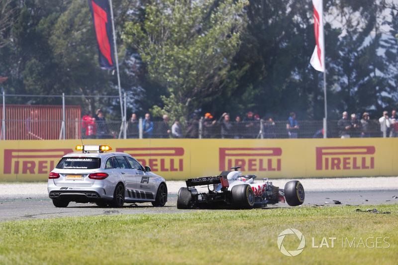 Una macchina ufficiale ferma accanto alla monoposto incidentata di Romain Grosjean Haas F1 Team VF-18