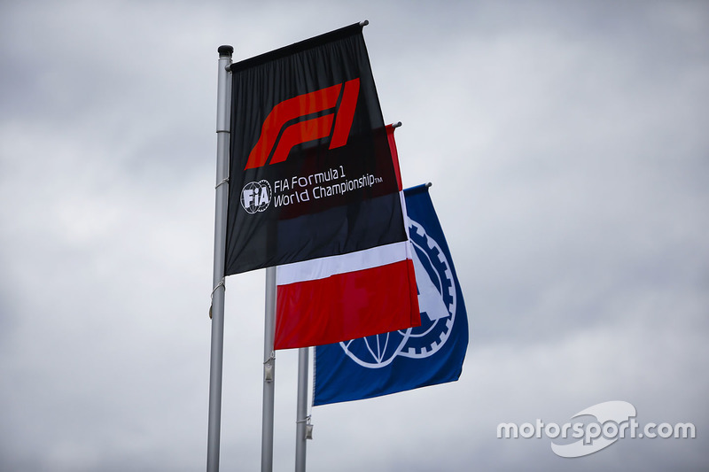 The Austrian flag flies alongside others displaying the Formula 1 and FIA logos