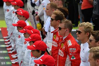 Les pilotes et les Grid Kids écoutent l'hymne national sur la grille