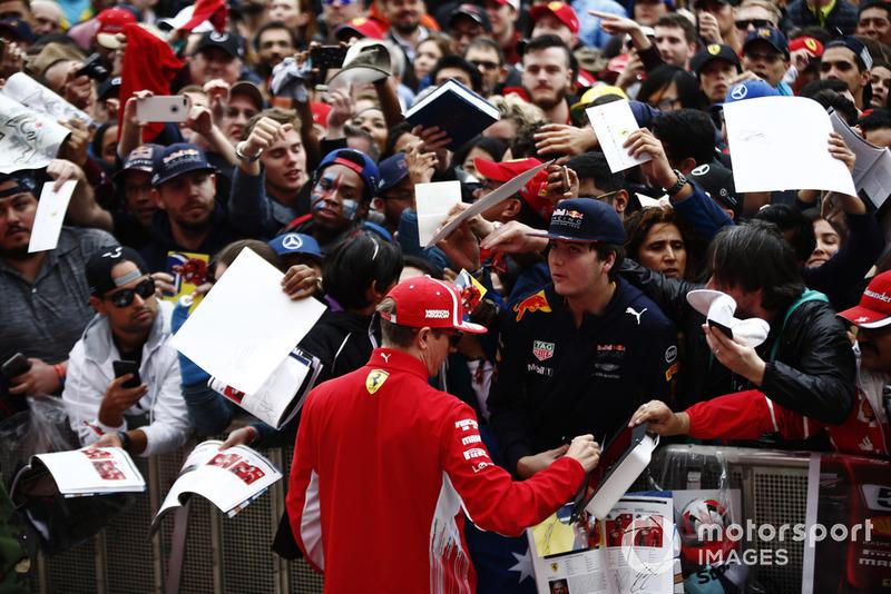 Kimi Raikkonen, Ferrari, signs an autograph